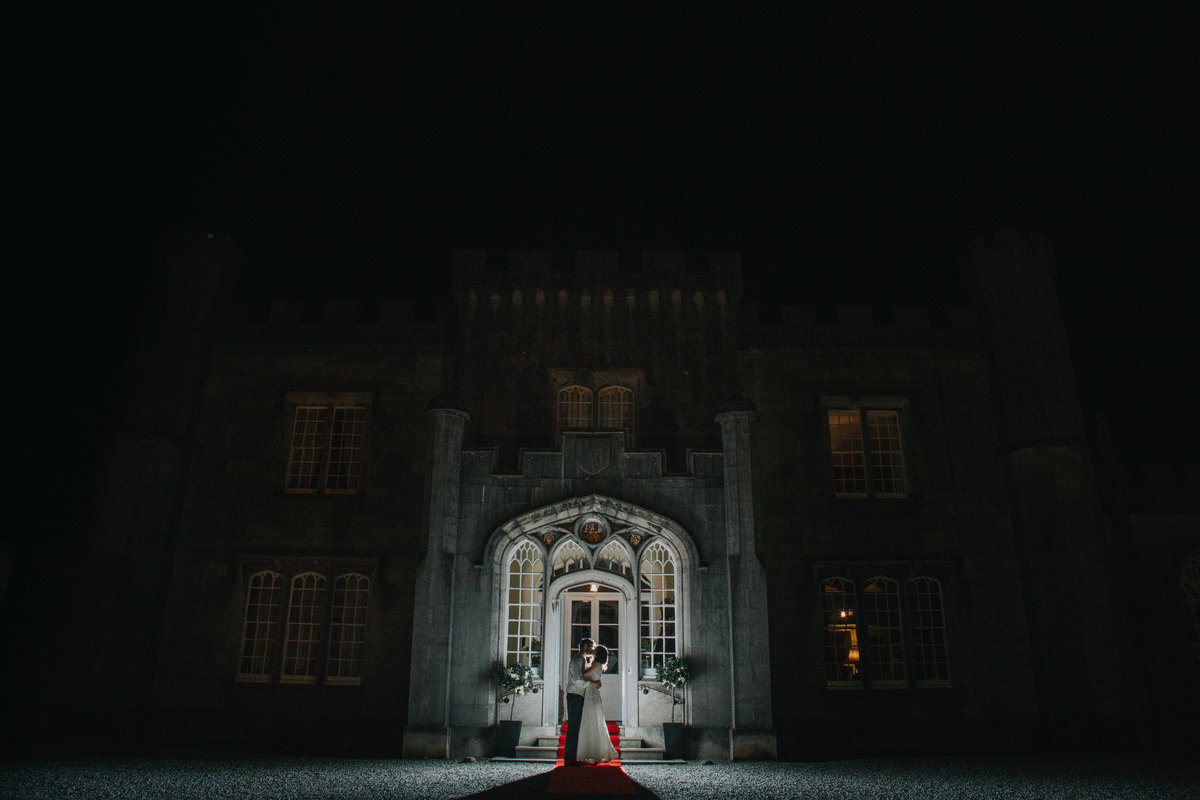 Couple backlight embracing outside of historic Leighton Hall, Lancashire by Lancashire Wedding Photographer Jono Symonds