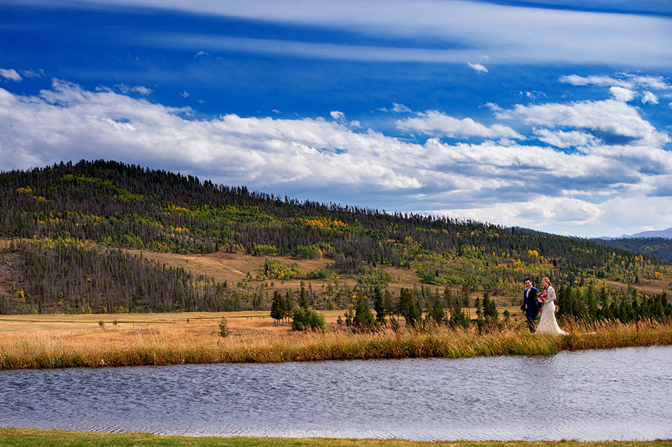 Granby-Colorado-Strawberry-Creek-Ranch-Wedding-Fire-on-the-Mountain-Wedding-Pops-of-Color-Fire-hot-colors-couple-walking-by-the-pond