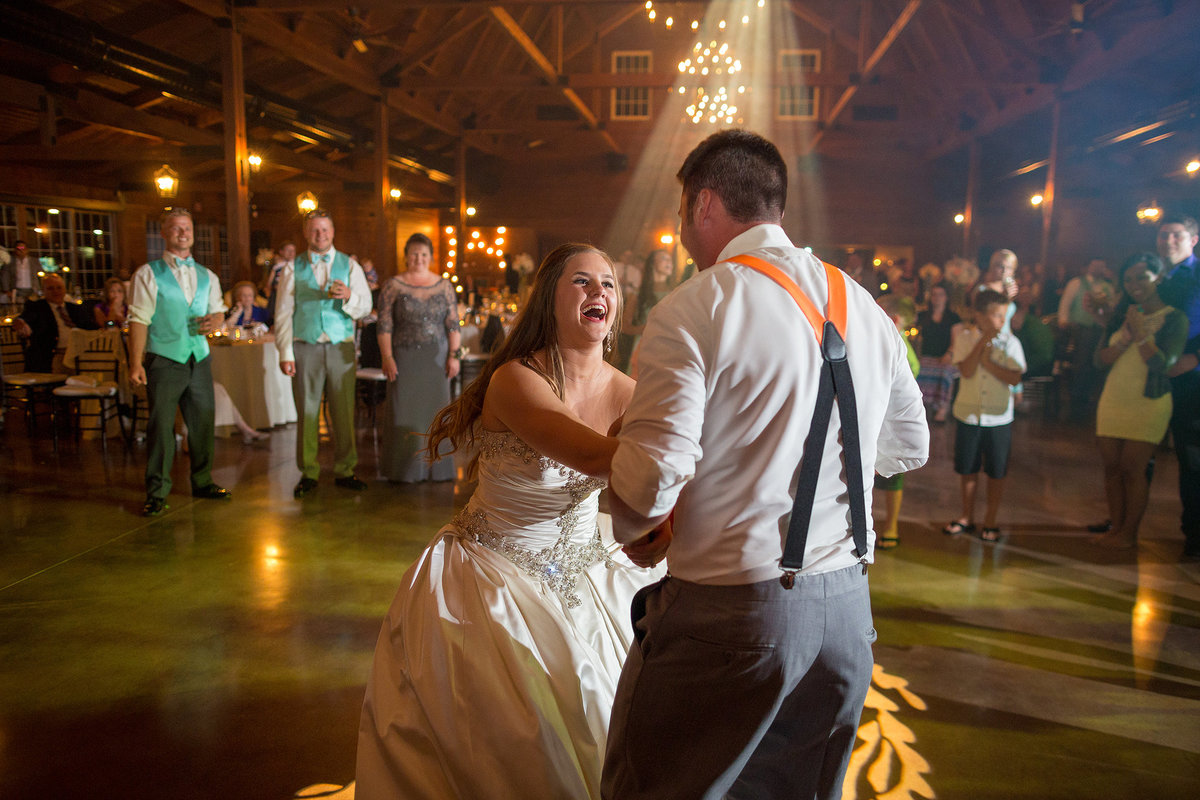 husband and wife laughing while dancing at their reception at orcahrd ridge farms the pavilion in rockton illinois