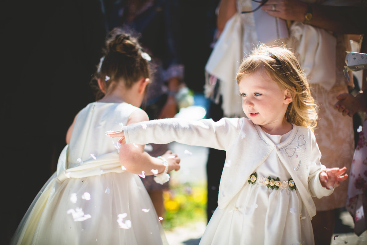 a flower girl is blowing bubbles at the bride and groom