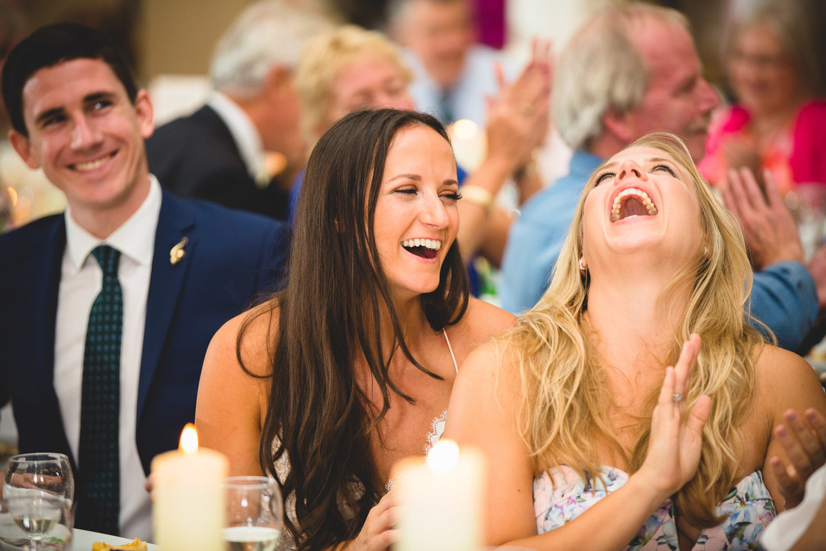bride and bridesmaid laughing in the wedding speeches
