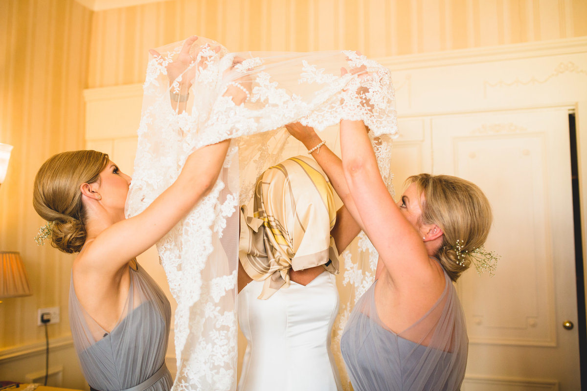 funny photo of bride putting wedding dress over her head protected hair