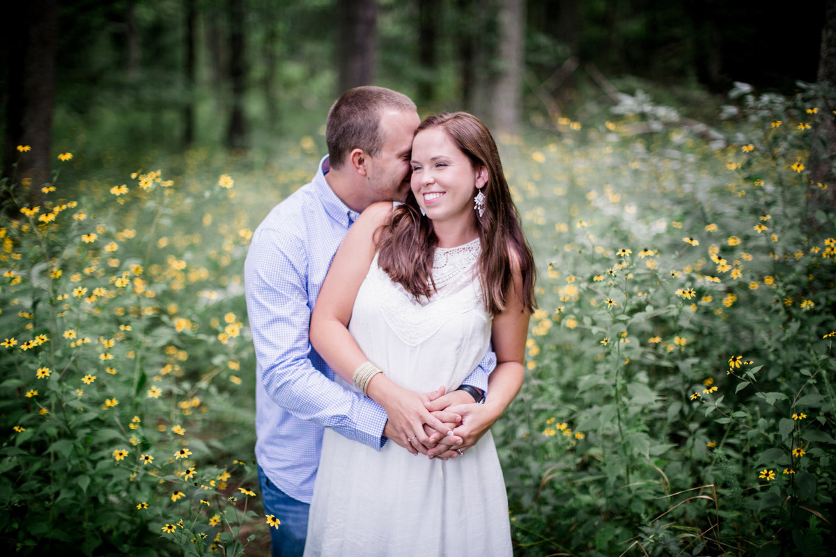 He wraps his arms around her from behind in the middle of wild flowers in Cades Cove engagement photo by Knoxville Wedding Photographer, Amanda May Photos.