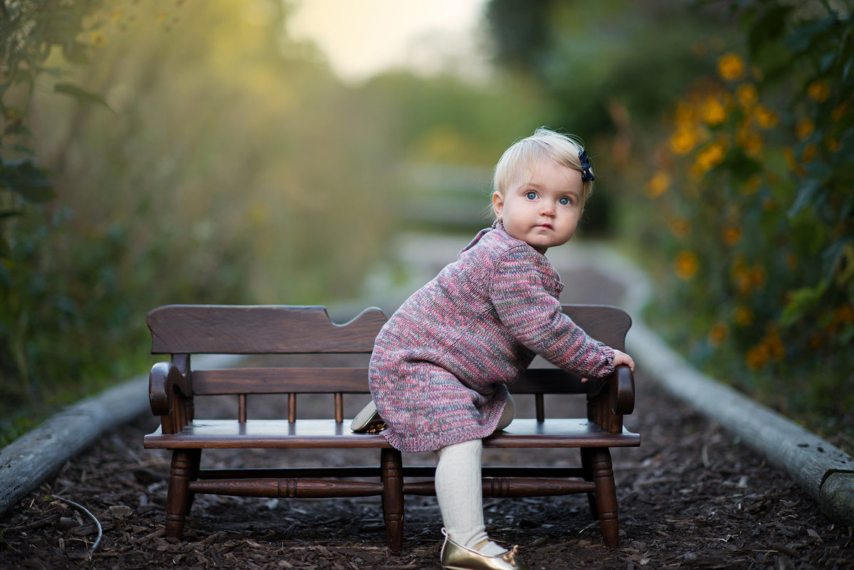 a girl poses on a bench in winnemac park