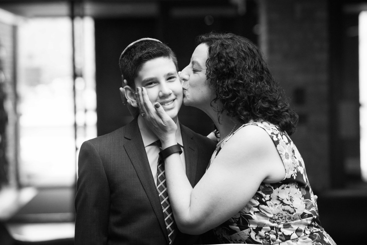 Bar mitzvah, mother kissing son on cheek, black and white, Chicago.