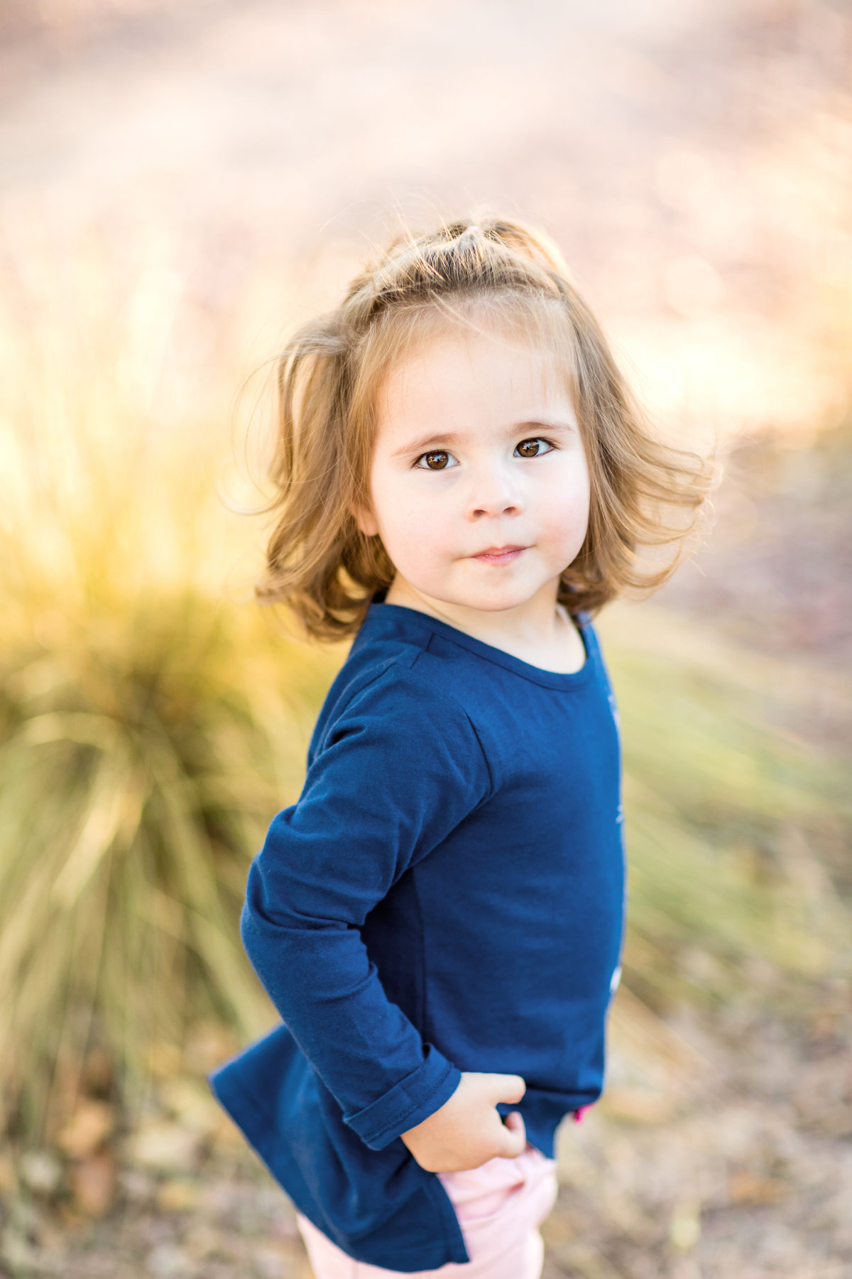 Toddler poses for a portrait outside