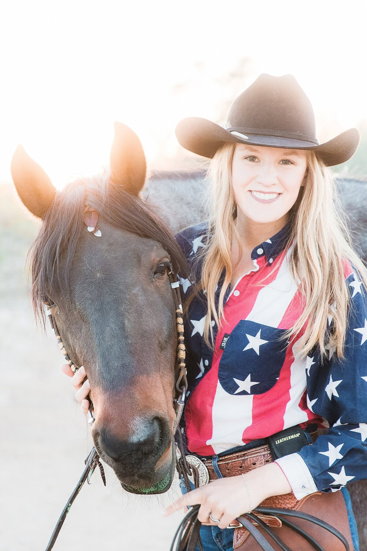 girl wearing an american flag shirt and cowboy hat, holding her horse's head