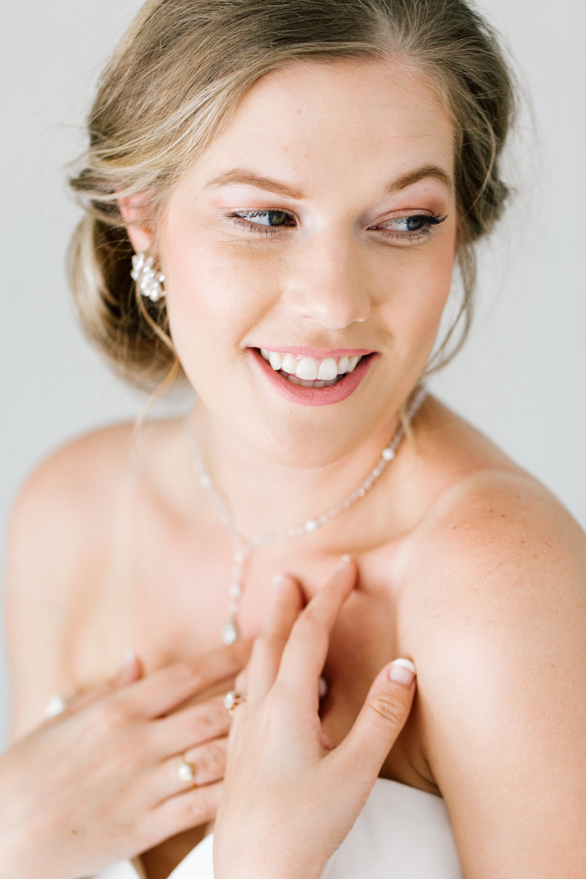 bride smiling and wearing jewelry
