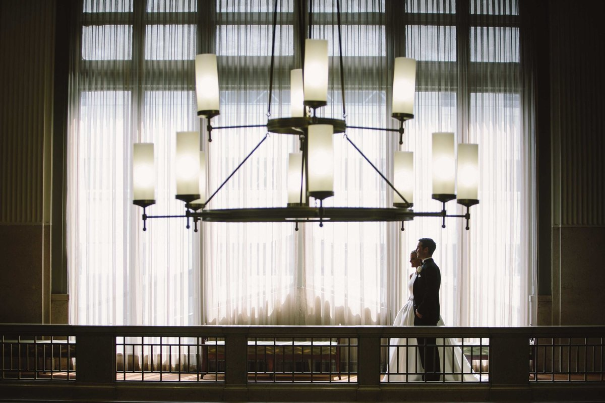 Bride and groom stands in front of window at Indianapolis wedding