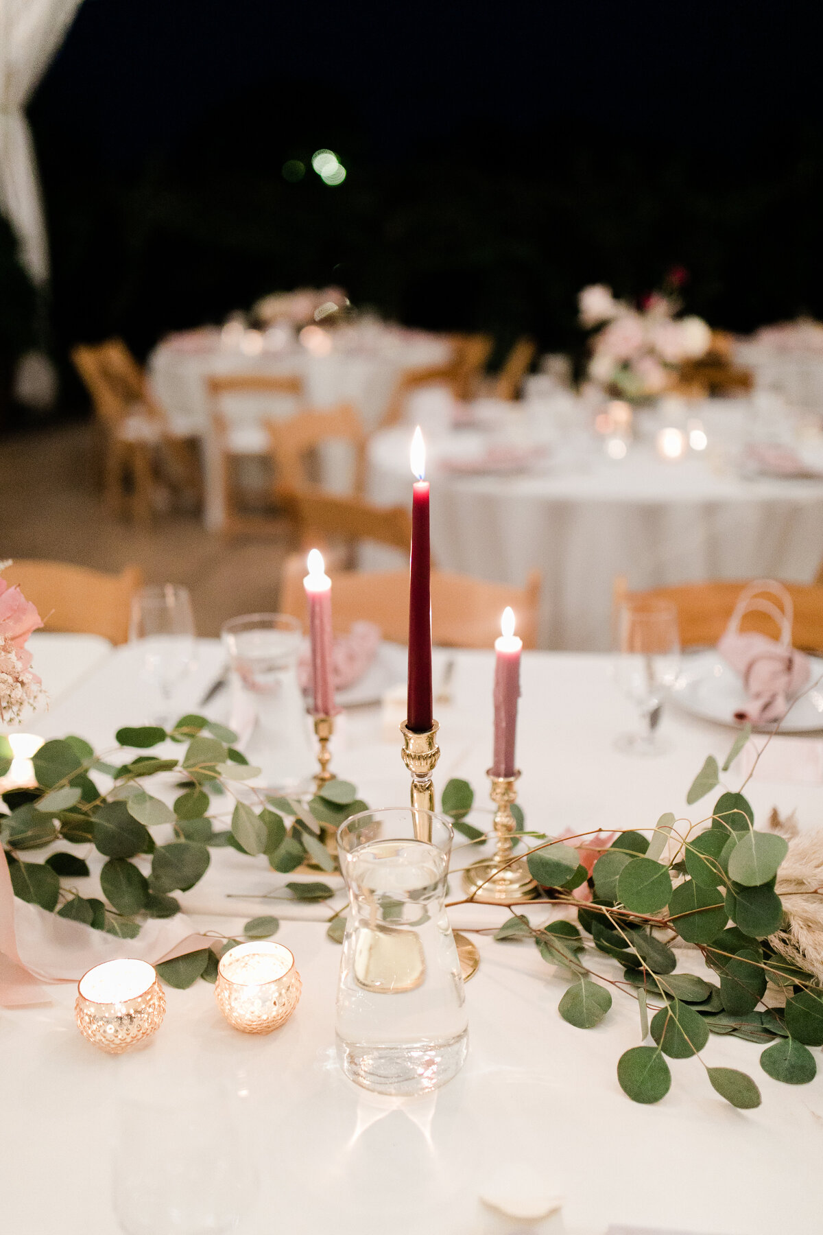 head table decorated with candle sticks and eucalyptus