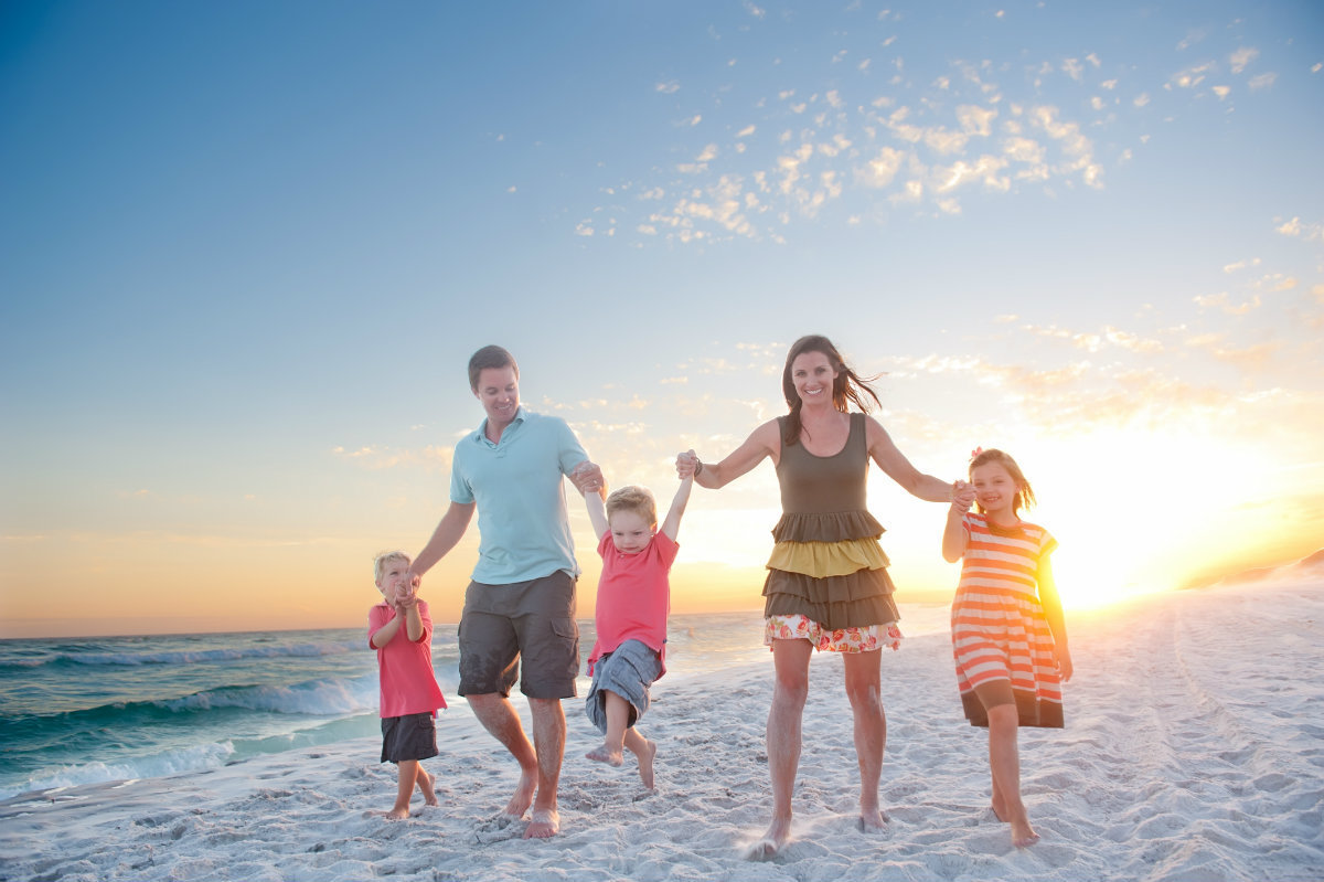 Family in colorful clothes playing on the beach in Watersound 30a