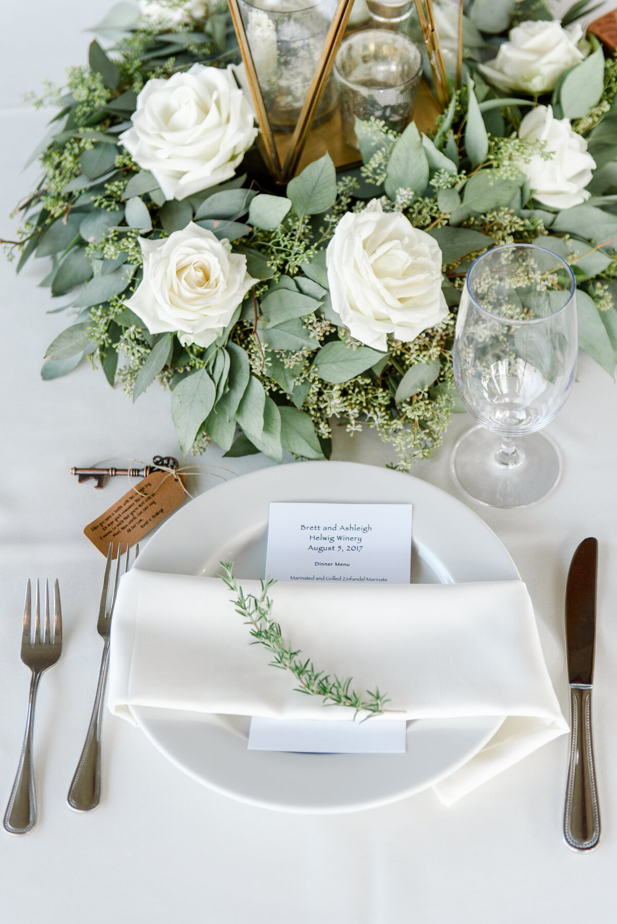 table with wood lantern greenery and white flowers