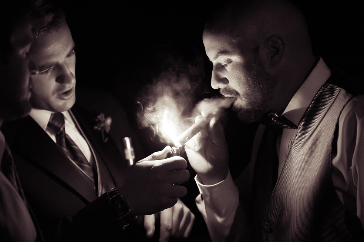groomsmen help groom light a cigar