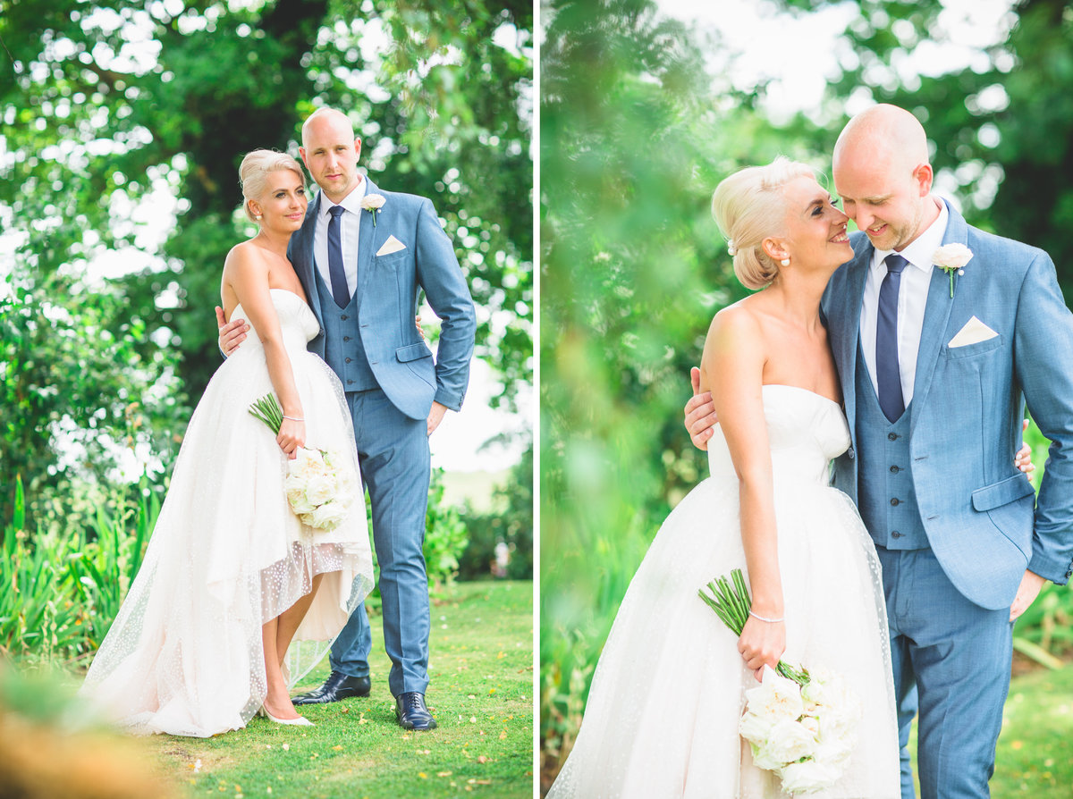 relaxed wedding photo of groom in blue suit and bride in a tulle wedding dress taken in summer