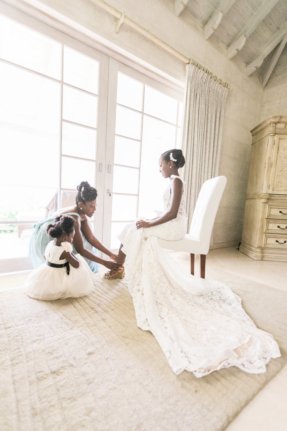 Bridesmaid and flower girl help bride put on her wedding shoes