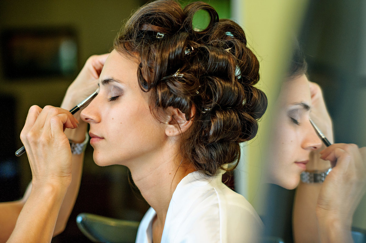 A bride getting her hair and makeup done before her wedding at her parent's house.