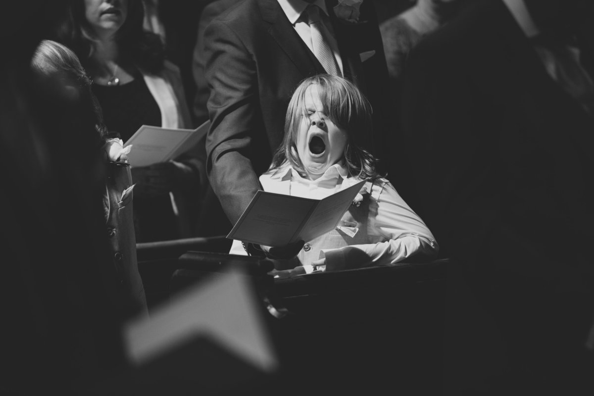 a kid is yawning during the wedding ceremony in the church bored