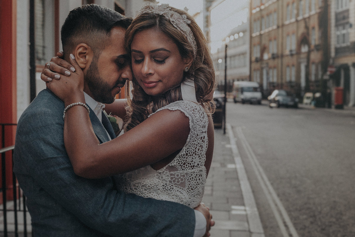 Asian couple embracing on the streets of London by Asian Wedding Photographer Jono Symonds
