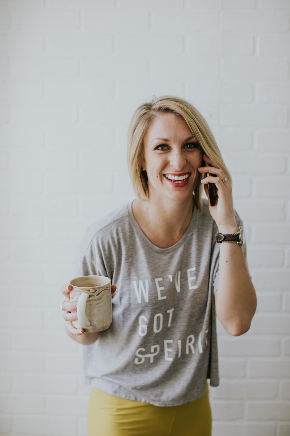 Work from home woman talks on the phone in front of white brick wall