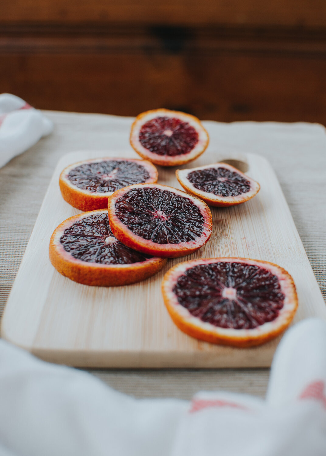 blood oranges sliced on wooden cutting board