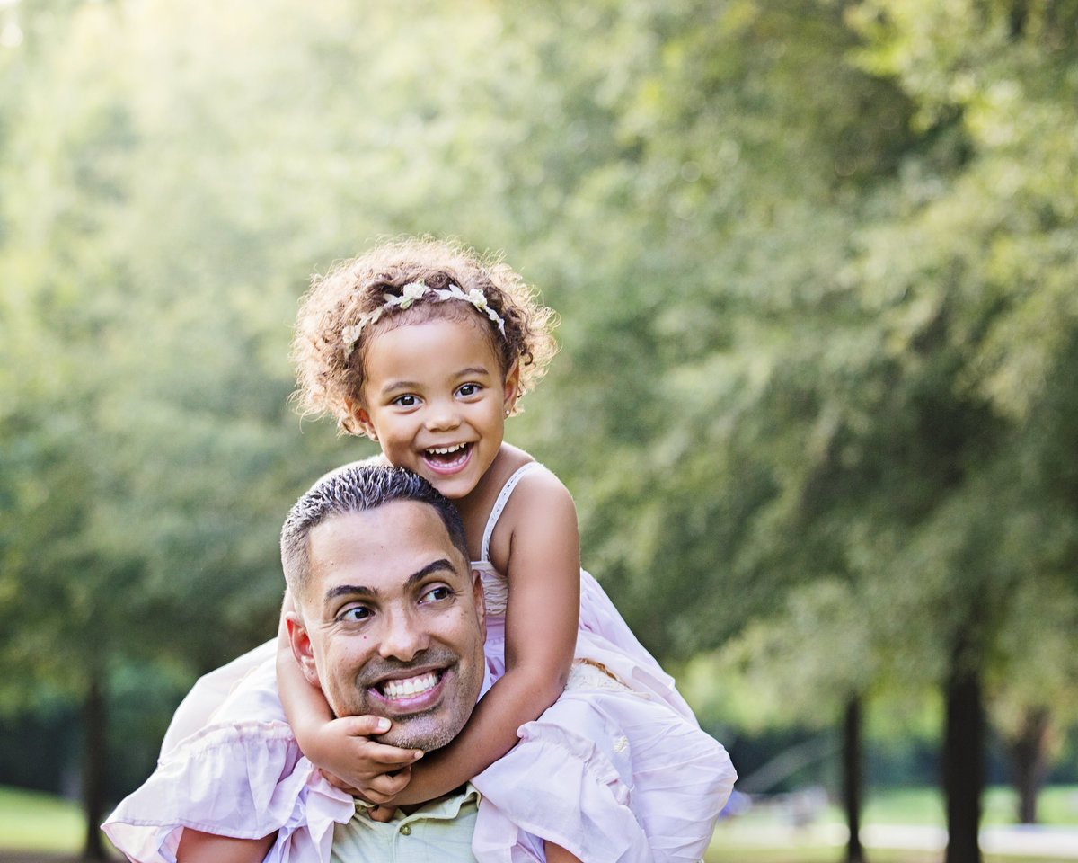 charlotte family photographer jamie lucido creates a playful father daughter image with child on father's shoulders