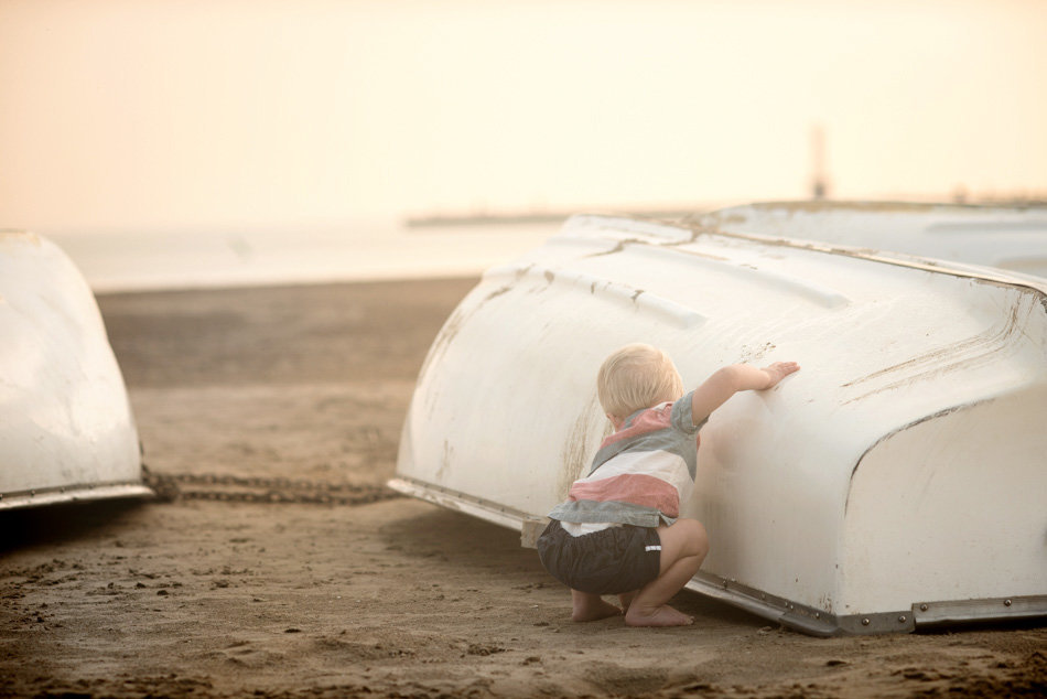 a boy plays in the boats on montrose beach