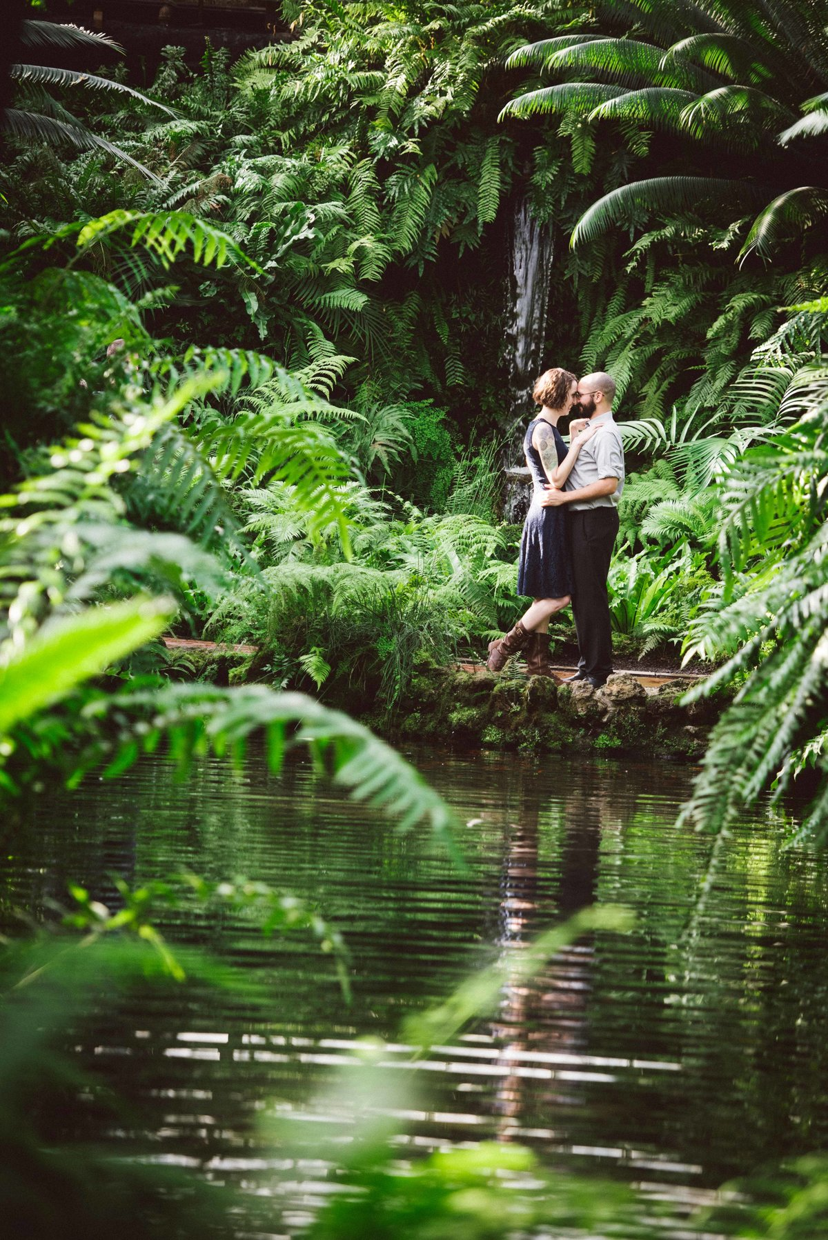 Engaged couple poses by water and ferns, Chicago IL.