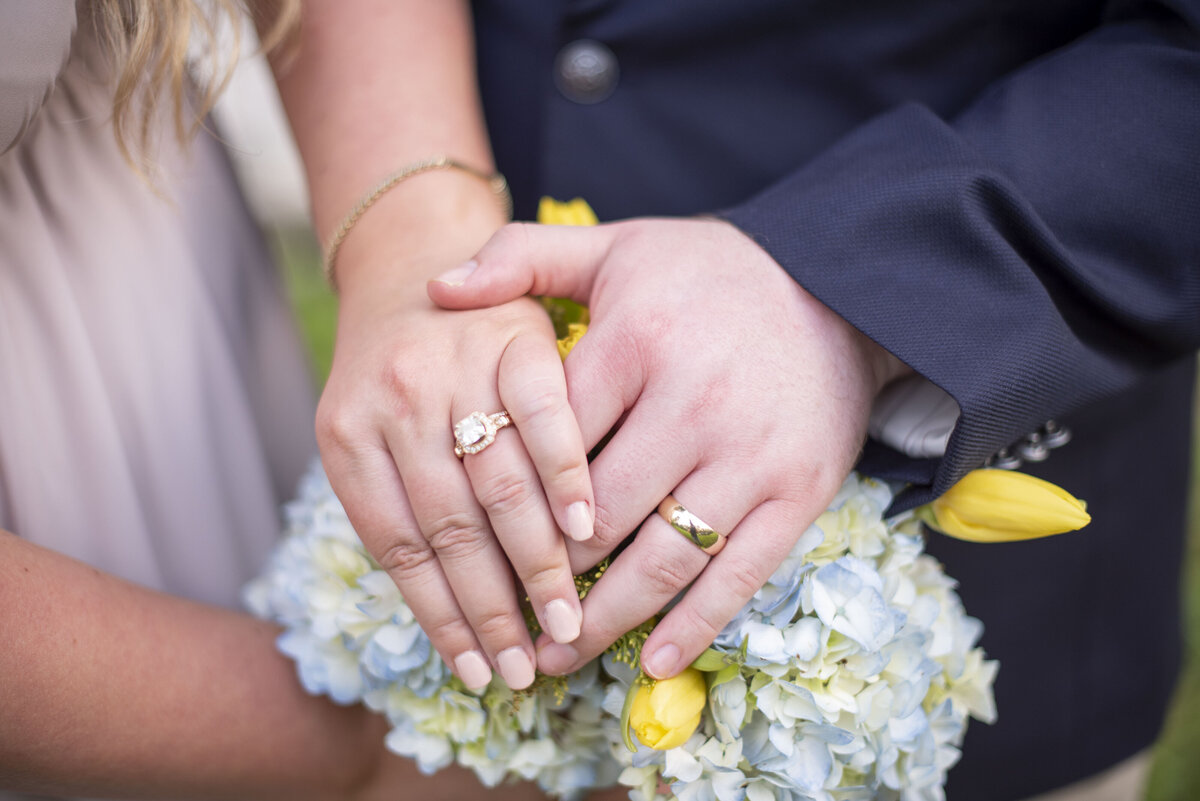 wedding rings on hands on top of bouquet