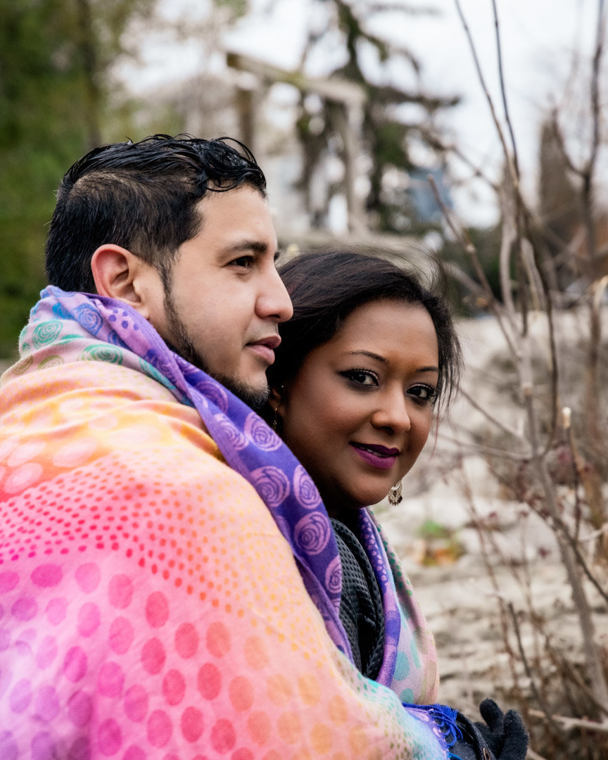 A couple sits at the duck pond covered with a bright coloured scarf while the guy looks over the water and the girl looks at the camera