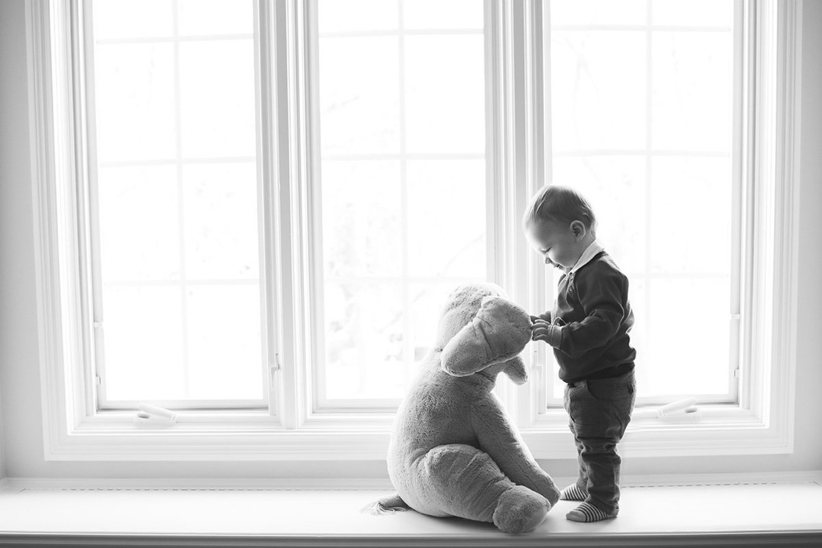 a toddler talks to his stuffed elephant in the window light