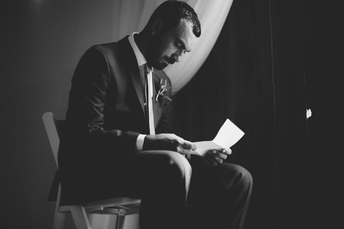 groom reading the note from his bride on wedding day
