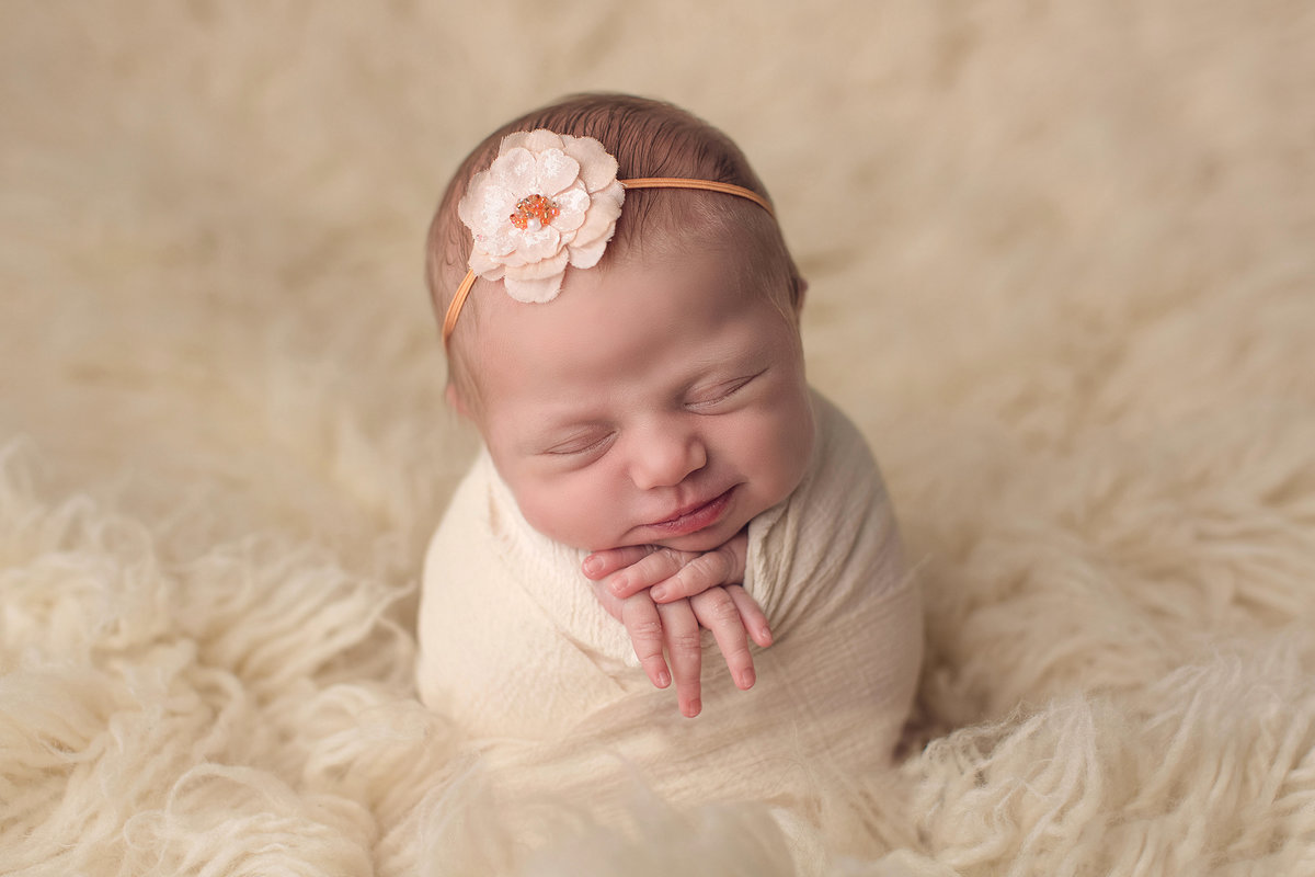 Baby wrapped in cream on fluffy fur backdrop wearing headband