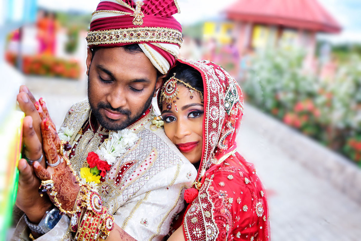 Hindu bride and groom embrace wearing traditional wedding clothes. Photo by Ross Photography, Trinidad, W.I..