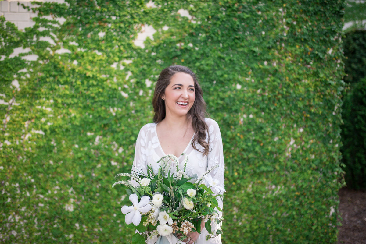 bride laughing standing in front of green ivy wall
