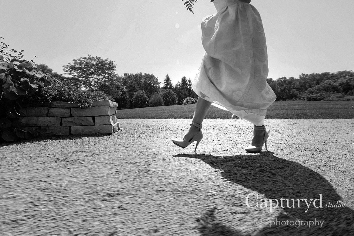 Bride walking in heals holding dress