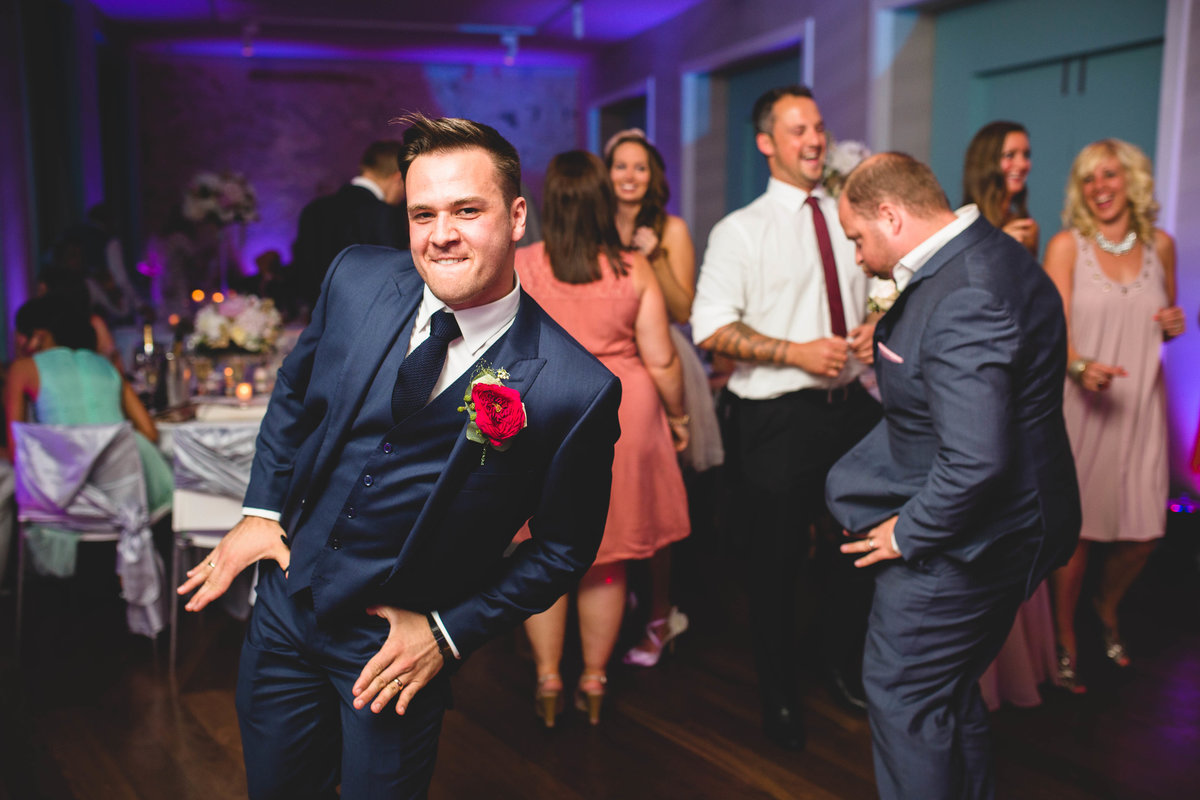 groom doing a funny dance at his wedding