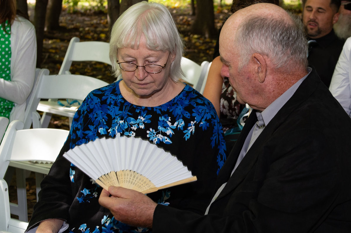 elderly man fans wife with at hot outdoor ceremony