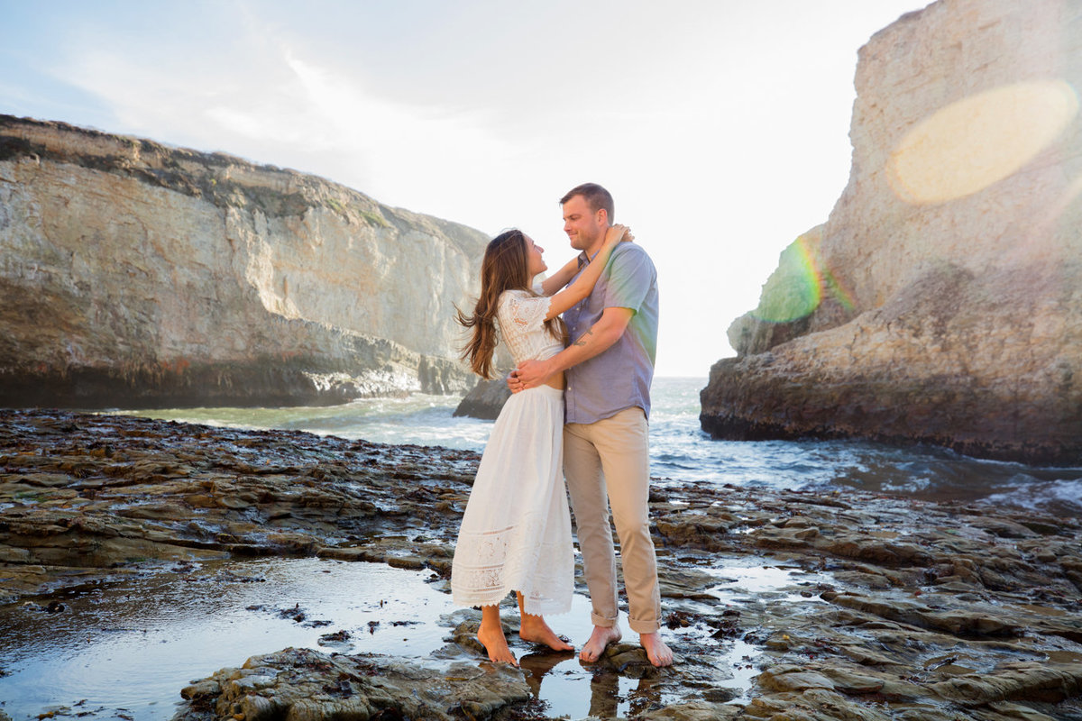 Engagement session in davenport, california, couple hugging on beach with natural light and backlit