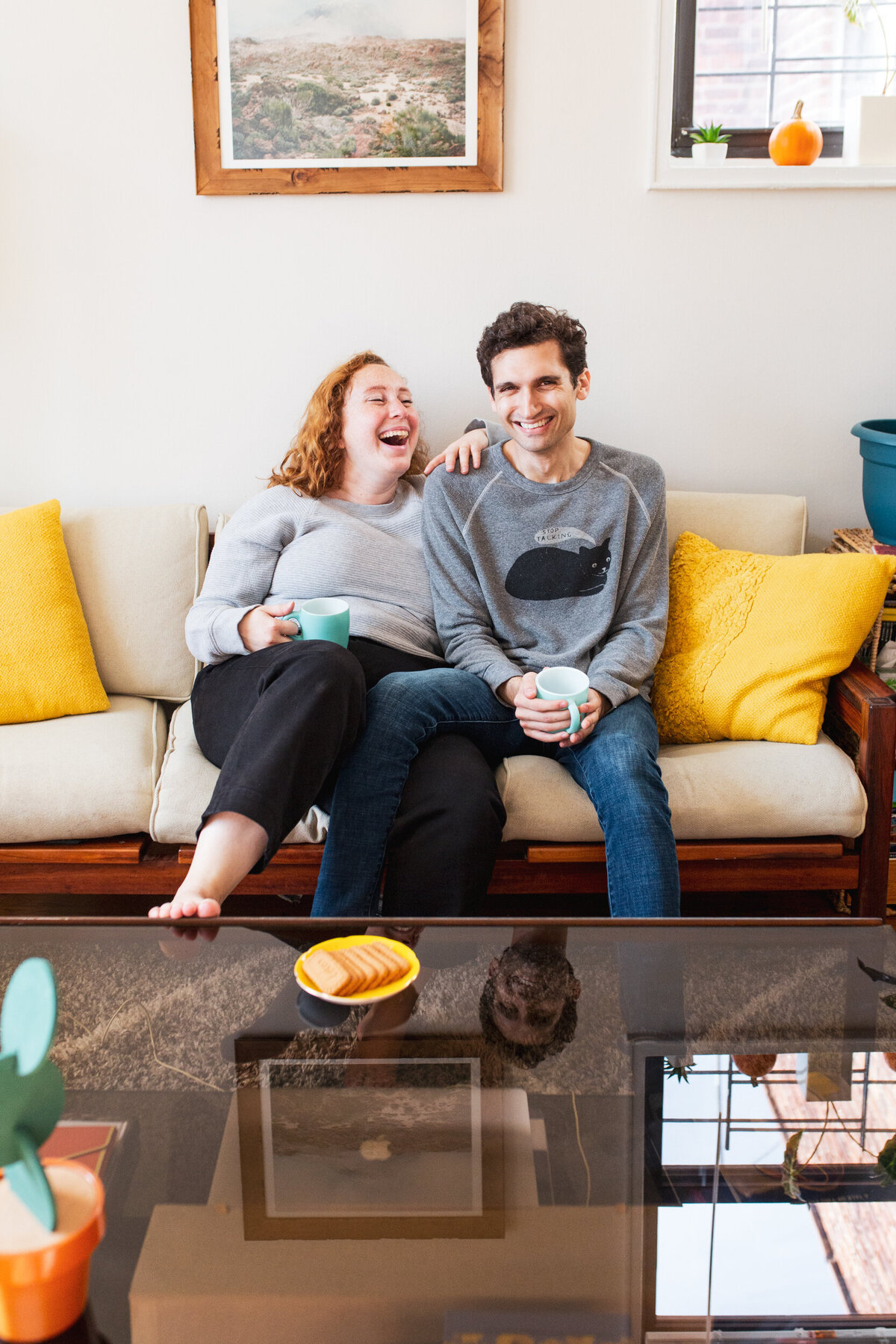 Relaxed, candid in-home couples session in Queens, New York. A curvy woman sits on the couch next to her fiance and they laugh while drinking tea.