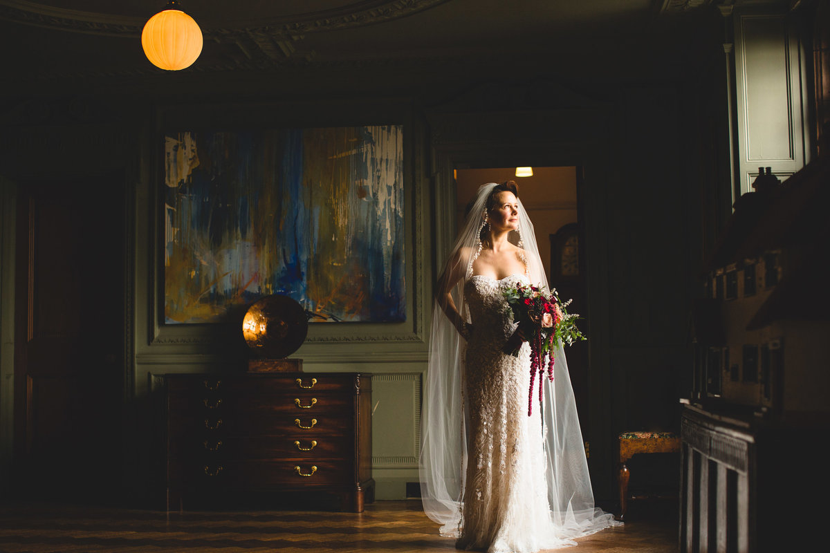a bride at thornton manor is looking out of the window in an elegant portrait