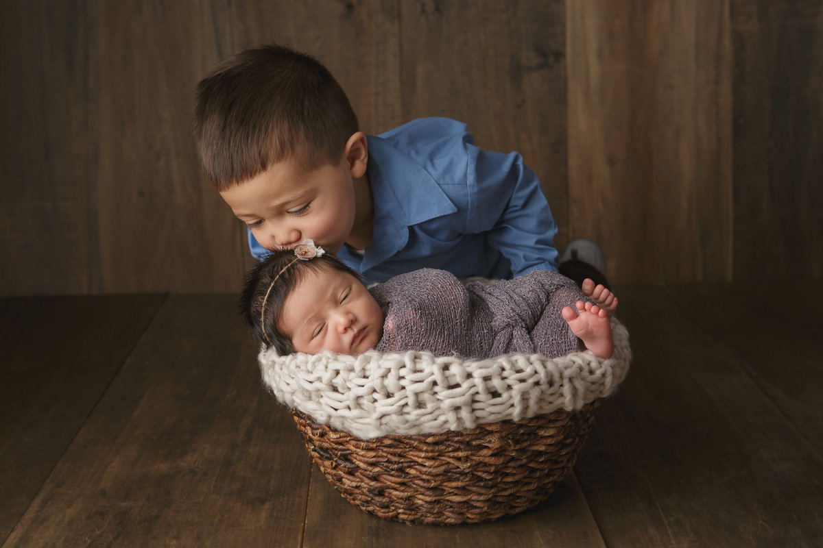 Big brother kissing his newborn baby sister sleeping in a basket prop in Cornwall NY photo studio by the best professional newborn baby photographer in the hudson valley