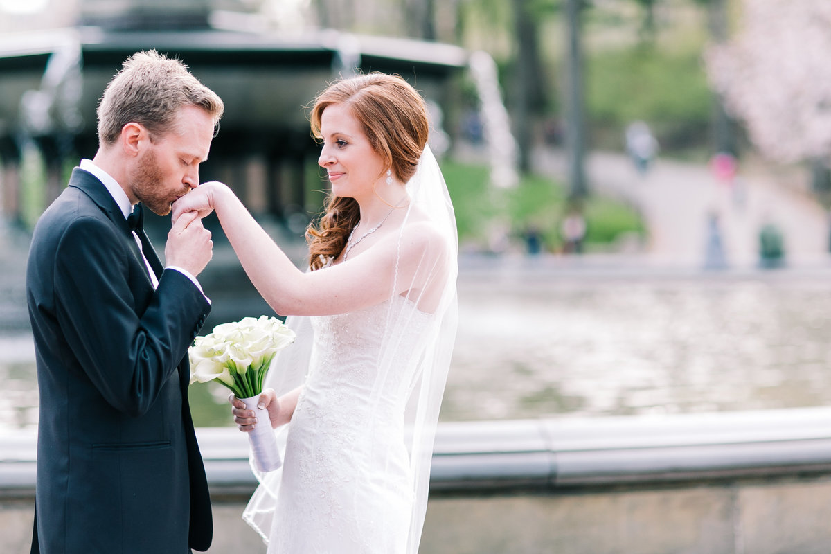 groom kissing his brides hand in central park