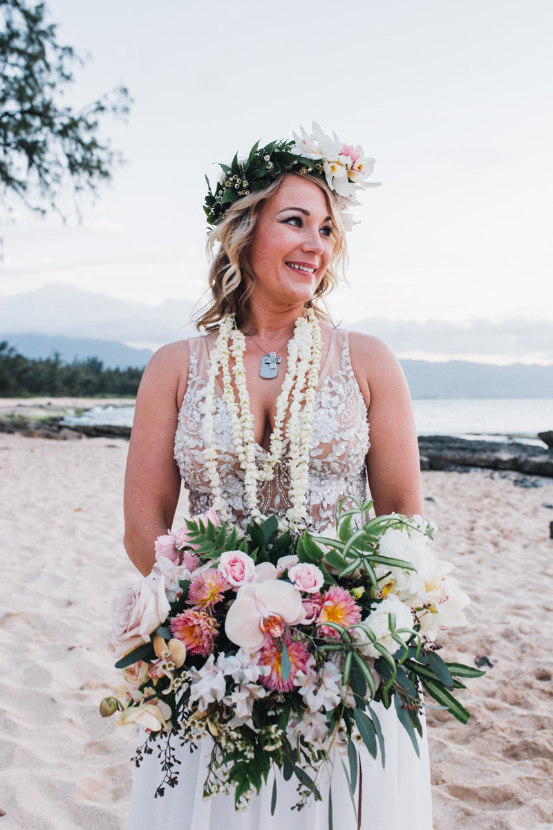 Bride with large boho bouquet and haku lei  on the beach