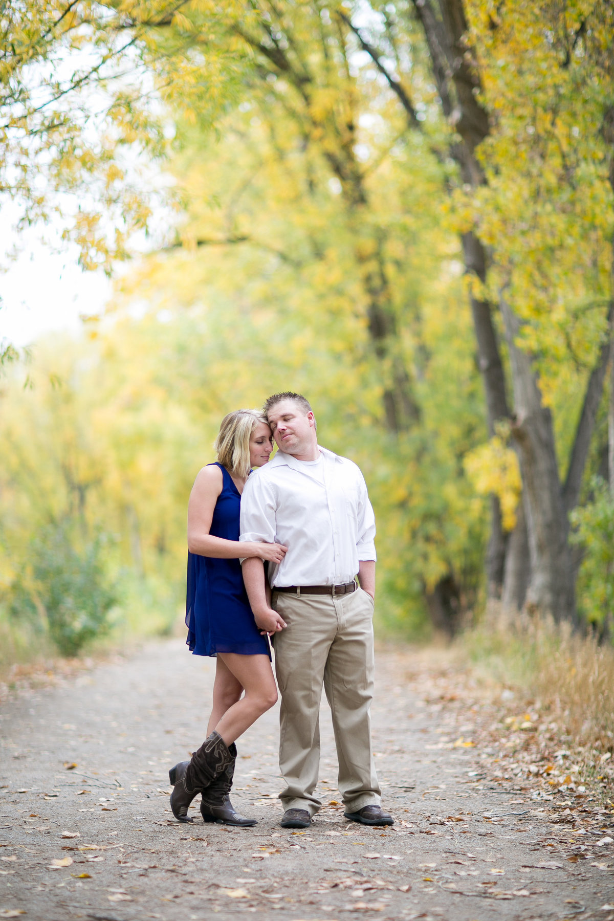 Girl in blue dress and cowboy boots snuggling her fiance during their fall engagement photos sessions