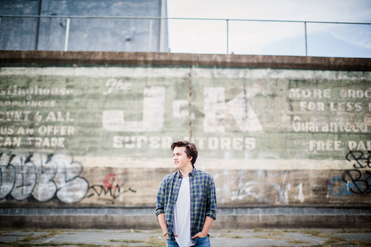 Boy senior standing in front of green wall in downtown Maryville  by Knoxville Wedding Photographer, Amanda May Photos.
