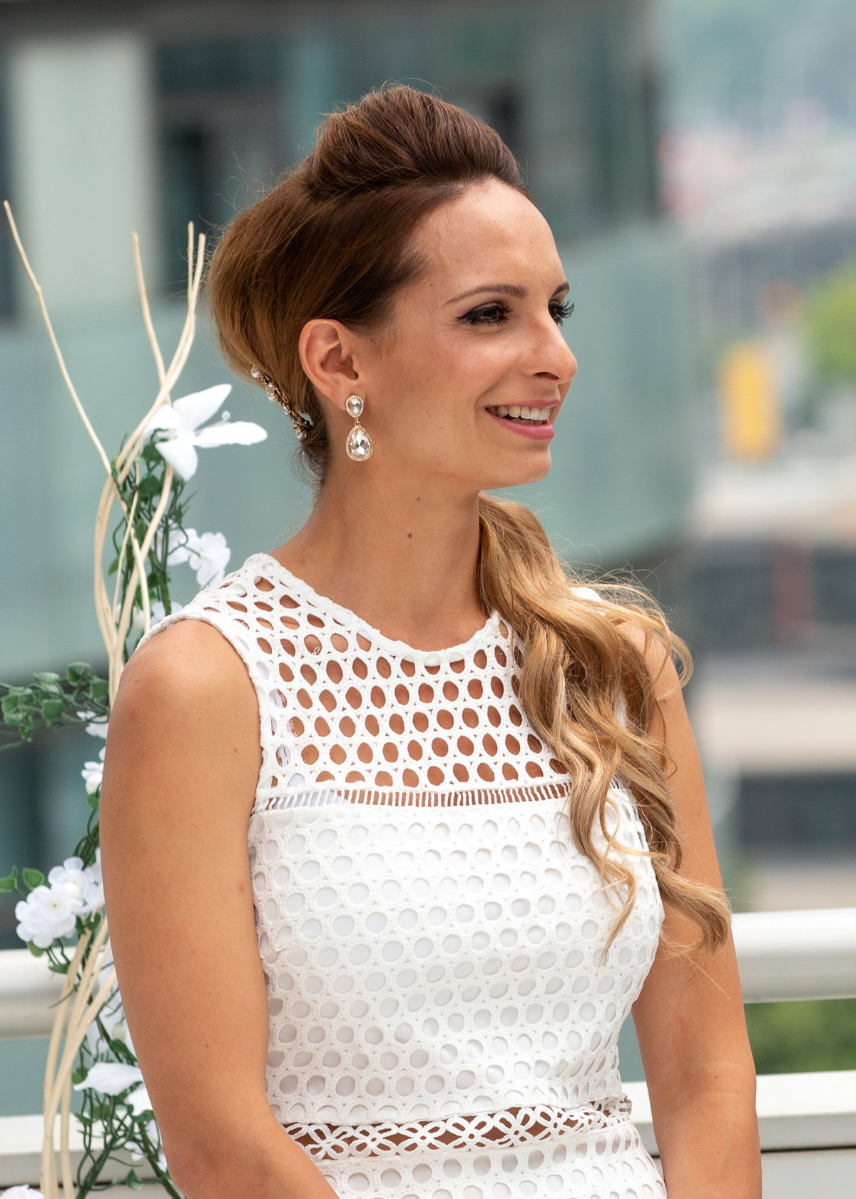 Bride wearing a modern white bridal dress smiling as she stands at the  Toronto rooftop wedding alter