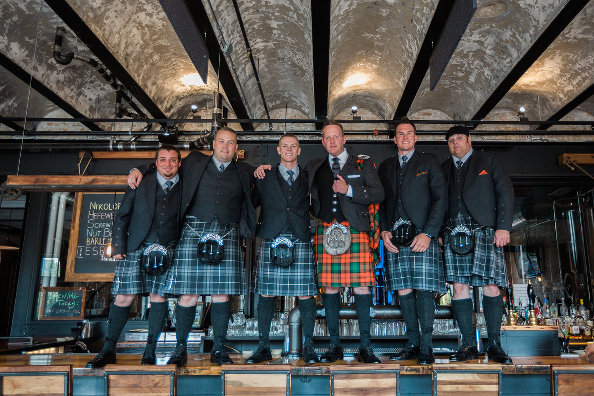 groomsmen standing on bar with kilts at prairie brewing company in rockford illinois