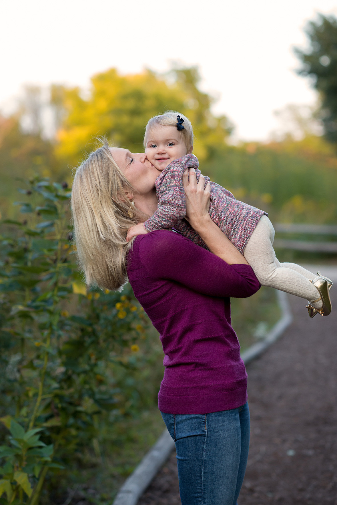 a mom kisses her daughter at winnemac park