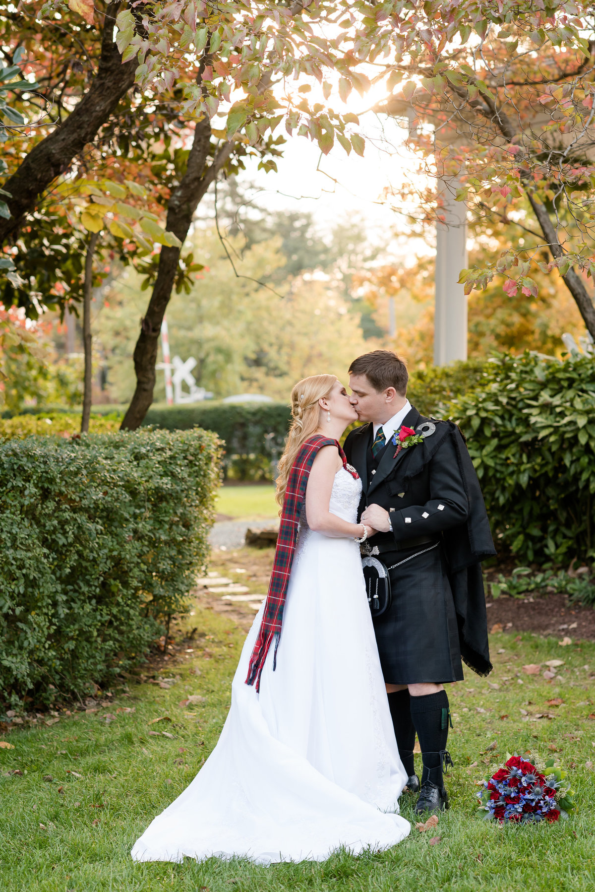 a groom wearing a traditional Scottish attire kissing his bride with a strapless dress at Burke Manor Inn