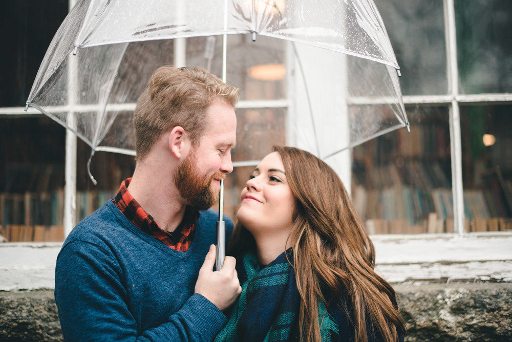 rainy day engagement photo couple under umbrella